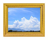Clouds in the blue sky and mountain on golden frame — Stock Photo