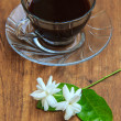 Black coffee on wooden table with Jasmine flower — Stockfoto