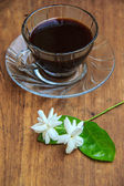 Black coffee on wooden table with Jasmine flower — Stock Photo