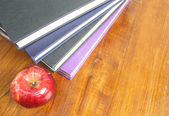 Red apple and old books on wooden tabletop — Foto de Stock