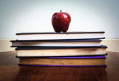 Red apple and old books on wooden tabletop — Stock Photo