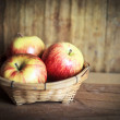 Red apple on wooden table with gray wall — Stock Photo