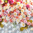 Beautiful rose fake flower on white mesh cloth — Stock Photo