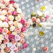 Beautiful rose fake flower on white mesh cloth — Stock Photo #38098019