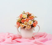 Bouquet of roses in white jug on wooden table and gray concrete walls — Stock Photo