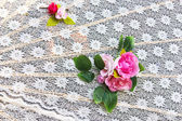 Pink rose fake flower on white mesh cloth — Stock Photo