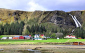 Icelandic houses and waterfall — Stock Photo