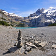 Stock Photo: Alpine lake and pyramid stone