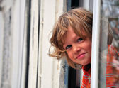 Smiling boy looking out of window — Stock Photo