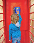 Kid in the telephone box — Stock Photo