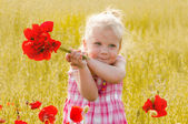 Beautiful little girl with a bouquet of red flowers stands on a — Stock Photo