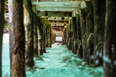 Abstract view under the pier getting narrowed toward the beach — Stock Photo