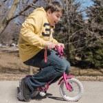 Big funny teenage boy riding small bike — Stock Photo