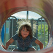 Child playing inside playground tube — Stock Photo