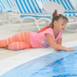 Child laying down at the pool edge and softly touching the water — Stock Photo