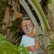 Little girl standing and hiding in tropical jungle — Stok fotoğraf