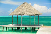 White sandy tropical beach with shed standing in the ocean — Stockfoto