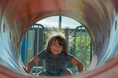 Child playing inside playground tube — Stock Photo