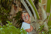 Little girl standing and hiding in tropical jungle — Stock Photo