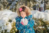 Child tying to blow a snow from her hands — Stok fotoğraf