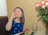Hungry beautiful little girl  looking up and eating sushi — Stock Photo