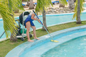 Girl cleaning the swimming pool border with broom — Stockfoto