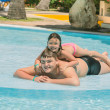 Little girl and teenage boy  having fun in garden swimming pool on sunny warm day — Stock Photo #47592455