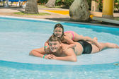 Little girl and teenage boy  having fun in garden swimming pool on sunny warm day — Stock Photo