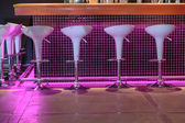 Night view of bar stand with cozy white decorative chairs — Stock Photo