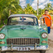Young adolescent standing beside his vintage retro classic car — Stock Photo #50271301