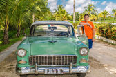 Young adolescent standing beside his vintage retro classic car — Stock Photo