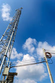 Single Mobile Tower and Electricity Post with Blue Sky. — Foto de Stock