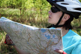 Summer theme. Woman on bicycle reading a map. — Stock Photo