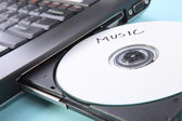 Closeup image of a laptop and a CD or DVD disc — Stock Photo