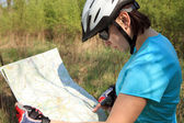Summer theme. Woman on bicycle reading a map. — Stockfoto