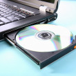 Closeup image of laptop and CD or DVD disc — Stock Photo #25898227