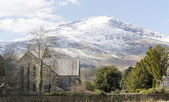 Snow covered mountain with St Marys church in Beddgelert, North Wales — Stock Photo