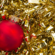 Red christmas bauble on gold tinsel background — Stock Photo #25756185