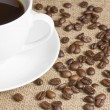 Stock Photo: Cup of black coffee with beans on hessian