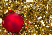 Red christmas bauble on gold tinsel background — Stock Photo
