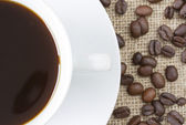 Cup of black coffee with beans on hessian background — Stock Photo