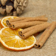 Cinnamon sticks, anise  and dried orange on hessian — Stock Photo