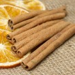 Stock Photo: Cinnamon sticks and dried orange on hessian