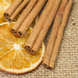 Stock Photo: Cinnamon sticks with dried orange on hessian