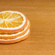Three slices of dried orange on wooden table — Stock Photo
