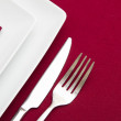 Red tablecloth with white square plates and red napkin — Stock Photo