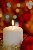 крем свеча с золотой мишурой, безделушка и размытие фона света — Стоковое фото