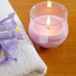 White towel with purple iris and candle spa concept — Stockfoto