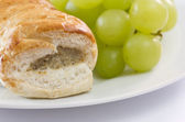 Sausage roll and grapes on a plate — Stock Photo