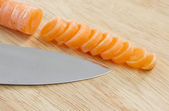 Carrot sliced on wooden chopping board — Stock Photo